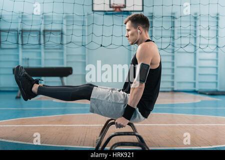 Vue latérale du jeune sportif faisant l'exercice de gymnastique sur les mains Banque D'Images