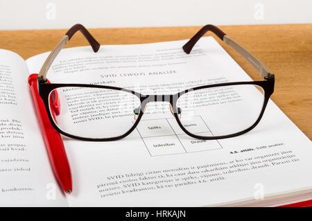 Les lunettes et stylo rouge sur les lieux livre ouvert sur la table en bois. Concept de l'étude Banque D'Images