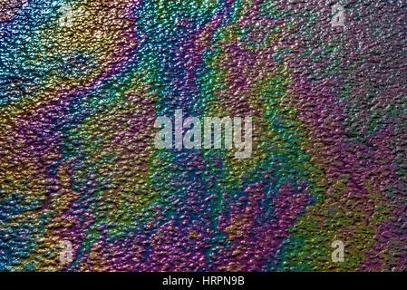 Effet arc-en-ciel causé par l'huile renversée sur le tarmac humide. Coloré. Banque D'Images