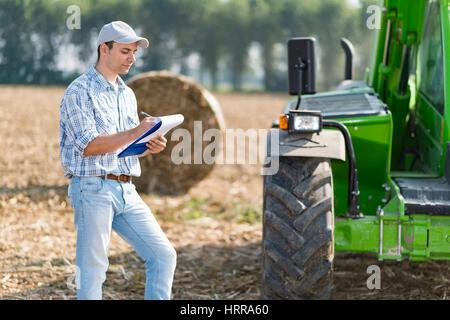Farmer écrit sur un document sur le terrain Banque D'Images