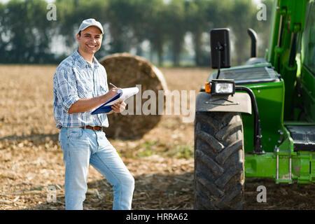 Smiling farmer écrit sur un document Banque D'Images
