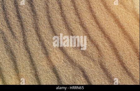 La texture du sable jaune. Le sable de la plage des modèles dans la lumière du soleil chaude soirée. Les lignes Banque D'Images