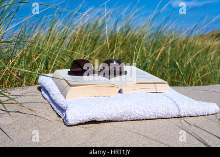 Livre sur la plage avec des lunettes une mauvaise herbe dans l'arrière-plan Banque D'Images