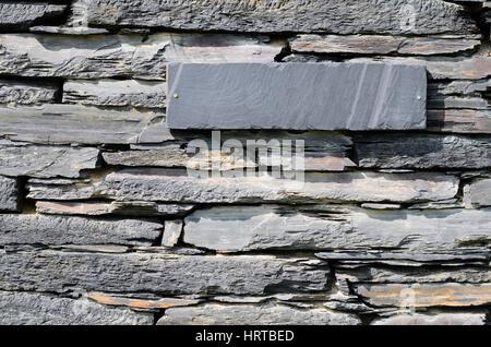 Sur une maison de pierres de schistes empilés à un mur Banque D'Images