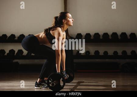 Femme fitness haltérophilie soulevé de terre. Modèle de remise en forme Salle de sport en haltérophilie fille. Banque D'Images