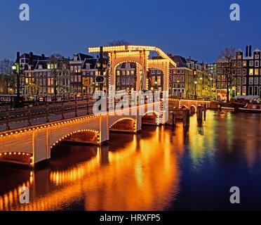 Magere Brug (pont Maigre) se reflétant dans la rivière Amstel la nuit, Amsterdam, Hollande, Pays-Bas Banque D'Images