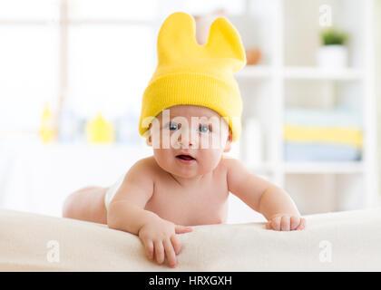 5d5c7e286f925e Peu drôle bébé garçon aux grands yeux bleus et des lunettes de soleil sur sa  tête · Bébé avec funny cap sur head lying on bed in nursery Banque D Images