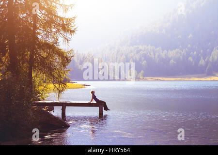 Happy woman sitting on the pier et souriant, de bonheur ou d'inspiration concept, profiter de la vie Banque D'Images
