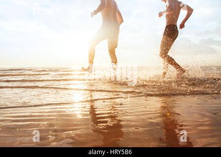 Les amis de s'amuser dans la mer au coucher du soleil plage, enfance heureuse Banque D'Images