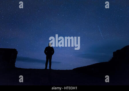 Homme debout sous les étoiles la nuit - Cornwall, uk Banque D'Images
