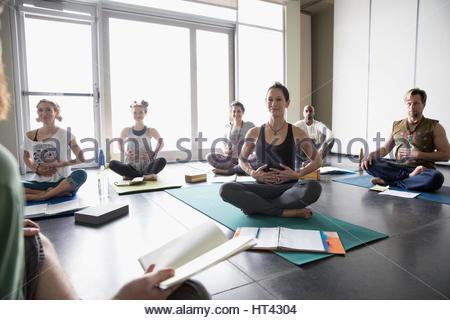 Cours de yoga avec des journaux pratiquant la respiration avec les mains sur ventre dans classe de yoga studio Banque D'Images