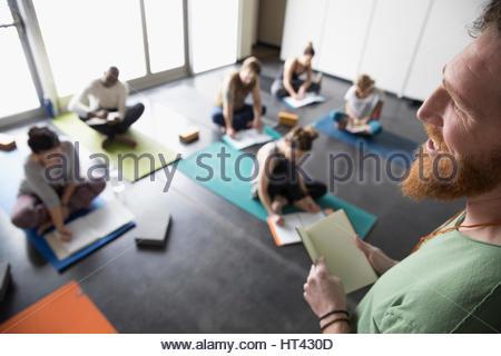 Professeur de Yoga de parler aux étudiants avec des journaux sur un tapis de yoga en classe de yoga studio Banque D'Images