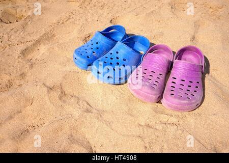 Les garçons et les filles en plastique rose et bleu sabots sur sunny beach Banque D'Images