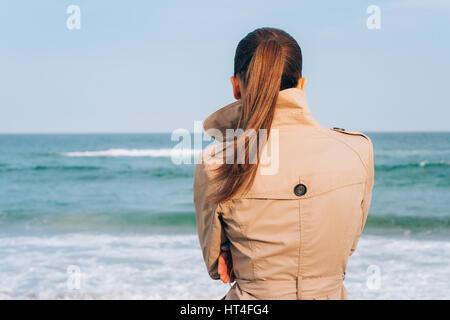 Brune en manteau beige ressemble à la mer, la vue de l'arrière Banque D'Images