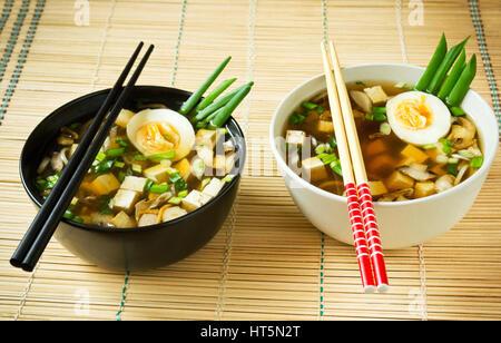La soupe miso dans des bols sur le tapis de bambou Banque D'Images