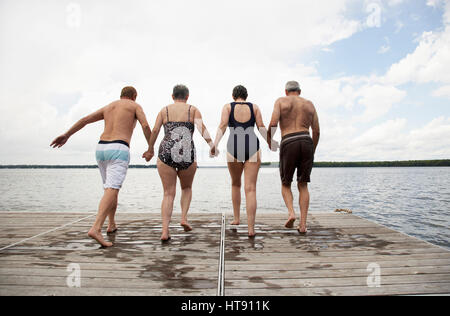 Des couples Jumping off Dock Banque D'Images