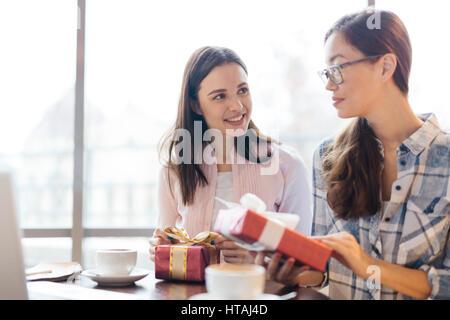 Scène sincère de deux jeunes femmes, un pays asiatique, le partage des dons et de parler à table dans le café assis Banque D'Images