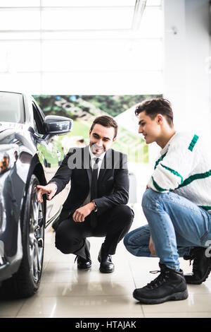 Regardez ces pneus. Jeune vendeur de voiture montrant les avantages de la voiture au client Banque D'Images