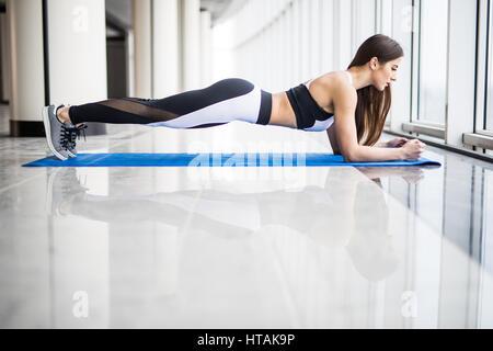 Perfect plank. Long side view of young Beautiful woman in sportswear faisant plank en se tenant debout en face de Banque D'Images