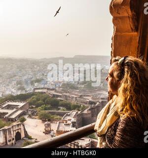 Une femme donne sur la ville de Jodhpur à partir d'une fenêtre en haut Fort Mehrangarh. Le Rajasthan, Inde.