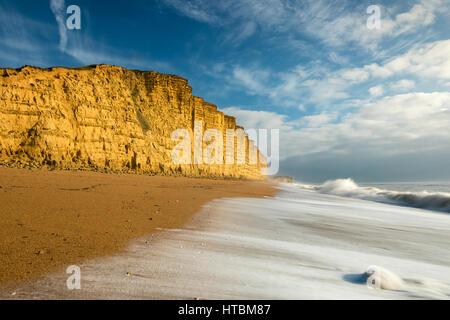 Vagues se brisant sur la plage sous falaise Est, West Bay, sur la côte jurassique, Dorset, England, UK Banque D'Images