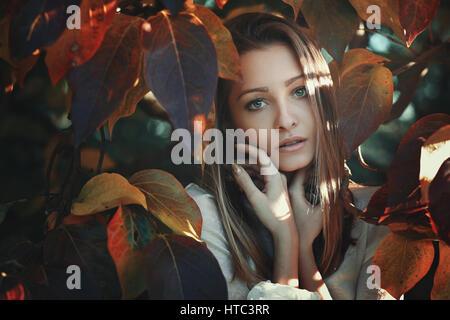 Belle jeune femme posant parmi les feuilles aux couleurs automnales Banque D'Images