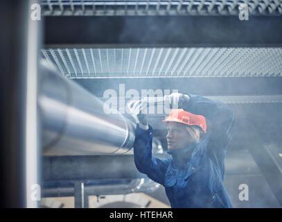 Technicien, mécanicien de casque orange le montage d'un support de conduite de réfrigération, Autriche Banque D'Images