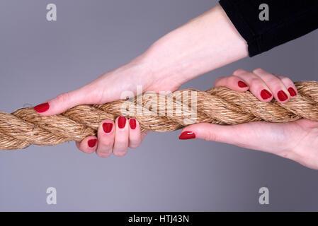 Woman's hands ongles peints avec une corde de serrage Banque D'Images