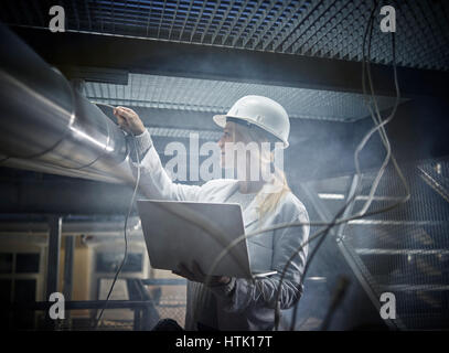 Jeune femme avec casque, sarrau blanc et l'ordinateur portable debout devant une usine industrielle, Autriche