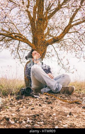 Jeune homme hipster de prendre des coups de près d'un arbre en fleurs au printemps Banque D'Images