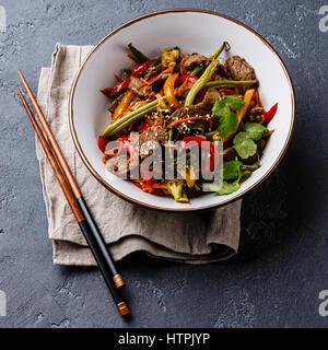 Sauté de boeuf du Sichuan avec des légumes dans un bol de pierre sombre contexte Banque D'Images