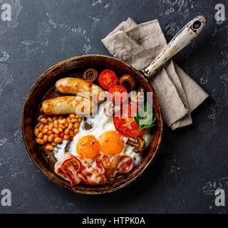 Le petit déjeuner anglais en plat de cuisson avec les œufs, saucisses, bacon et haricots sur pierre sombre contexte Banque D'Images