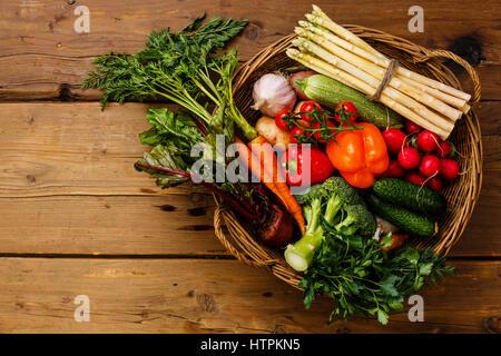 Des légumes frais dans le panier sur fond de bois Banque D'Images