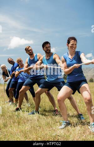 Gens jouer remorqueur de la guerre au cours d'obstacle dans boot camp Cours de formation Banque D'Images