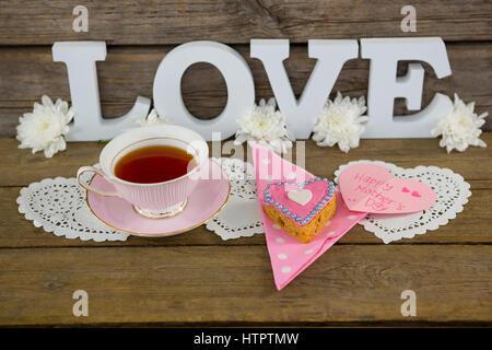 Cookies, thé, fleurs et happy mothers day card avec amour texte sur planche en bois Banque D'Images