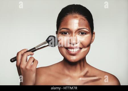 Portrait de contour et mettre du maquillage sur modèle féminin. Femme appliquant le maquillage sur son visage avec Banque D'Images