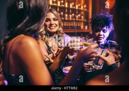 Groupe d'amis ayant des boissons à la discothèque. Les jeunes bénéficiant dans un bar.