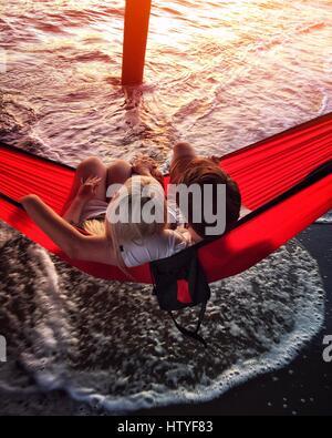 Couple assis dans un hamac sous la jetée, Aptos, Californie, Amérique, USA Banque D'Images