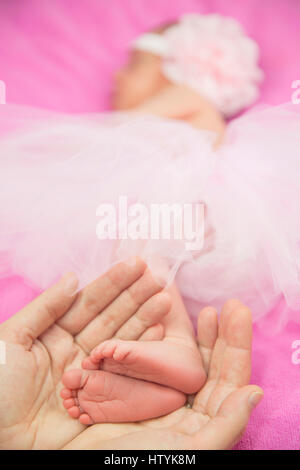 Woman's hands holding a baby girl's feet