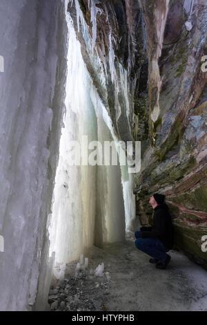 Un homme accroupi à l'intérieur d'une grotte de glace formée derrière Buttermilk Falls au cours de l'hiver, à Hamilton, Banque D'Images