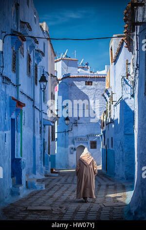 Homme avec une robe traditionnelle marche dans la médina de Chefchaouen bleu, Maroc.