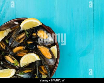 Les moules cultivées de corde dans une sauce à l'ail et l'échalote avec des tranches de citron