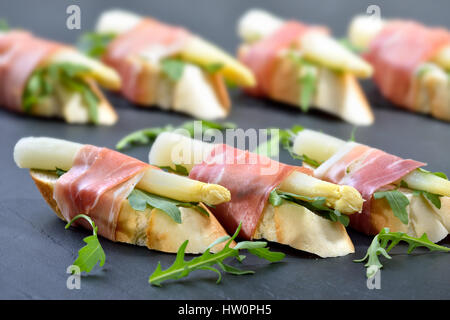 Morceaux délicieux avec les asperges blanches sur feuilles de roquette enveloppé de prosciutto Italien
