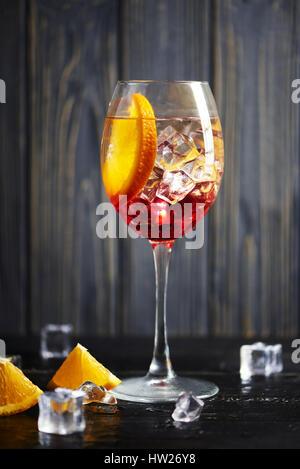 Un cocktail rafraîchissant avec orange rouge isolé sur un fond de bois avec des oranges et de la glace