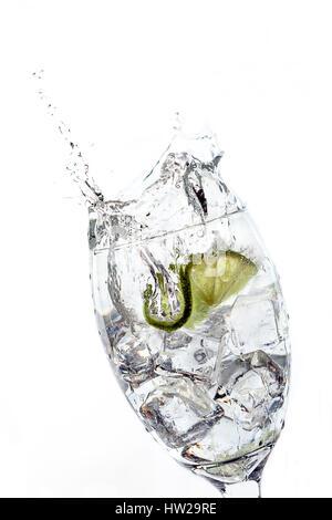 Tranches de lime a fait un splash après être tombé dans un verre d'eau glacée. Banque D'Images