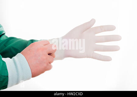 Close up of male doctor's mains mettre des gants chirurgicaux stériles sur contre fond blanc Banque D'Images