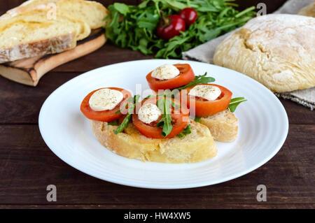 Bruschetta à la roquette, tomates, mozzarella, huile d'olive sur les tranches de chiabatta. Un petit-déjeuner léger. Banque D'Images