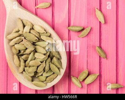 Cuillère pleine de gousses de cardamome entières Banque D'Images