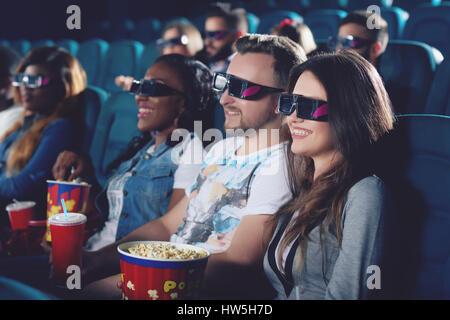 Friends watching movie en cinéma et sourire ensemble. Banque D'Images