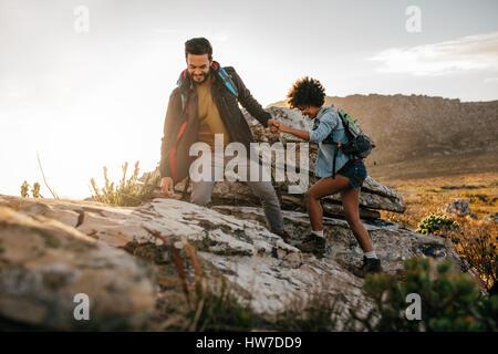 Jeune homme ami aidant à monter la roche. Jeune couple en randonnée dans la nature. Banque D'Images